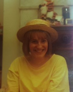 Photo of young Rachel wearing a straw hat and a yellow t-shirt. Finding treasure.
