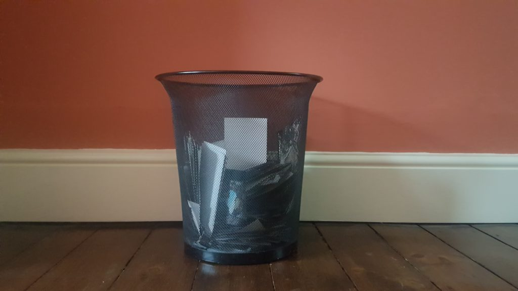 Rubbish bin full of discarded photo prints. Decluttering photographs. Declutter photos.