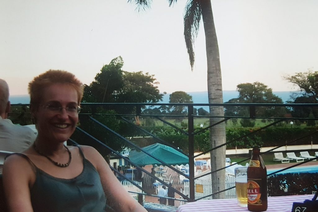 Rachel Papworth, online international professional organiser, from Green and Tidy, sitting by a table with a beer in Uganda in 2004. Rachel found this photo by decluttering digital photos.