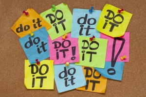"Lots of multi-coloured notes with ""Do it"" written on them, pinned to a corkboard"