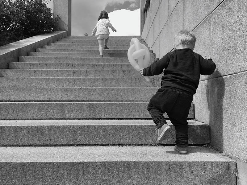 Two children climbing steps. The boy is behind struggling to keep up with the girl in front. This picture is illustrating a post about how to avoid feeling overwhelmed when you can't keep up with the stuff you need to do.